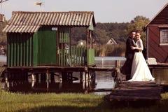 Bruid en bruidegom op houten brug dichtbij meer Stock Afbeeldingen