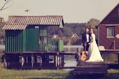 Bruid en bruidegom op houten brug dichtbij meer Royalty-vrije Stock Afbeeldingen