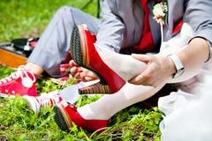 Bruid en bruidegom op rode schoenen stock foto's