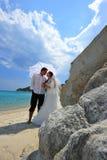 Bruid en bruidegom op tropisch strand onder paraplu Royalty-vrije Stock Afbeeldingen