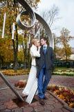 Bruid en bruidegom over ijzercijfer aangaande de herfst Royalty-vrije Stock Afbeeldingen