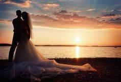 Bruid en bruidegom samen op een achtergrondzonsondergang Royalty-vrije Stock Foto