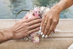 Bruid en Bruidegom Showing Wedding Rings op de Bovenkant van Boeket royalty-vrije stock afbeelding
