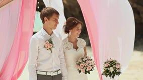 Bruid en bruidegom tegen de achtergrond van een bloemenboog Huwelijksceremonie bij het strand van de Filippijnen stock videobeelden