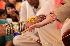 Bruid en bruidegom toetredende handen tijdens een Indisch huwelijksritueel Stock Foto's