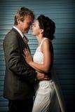 Bruid en Bruidegom wat betreft neuzen tegen een blauwe muur Royalty-vrije Stock Fotografie