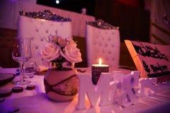 Bruid en Bruidegom Wedding Seats en Huwelijkslijst in Roze Licht Stock Fotografie