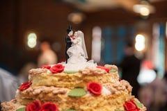 Bruid en bruidegomcijfers van suiker bovenop huwelijkscake die worden gemaakt stock foto