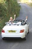 Bruid en Bruidegomdriving away in Verfraaide Auto stock foto's