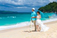 Bruid en bruidegomgang langs de tropische kust met blauwe paraplu Stock Afbeelding