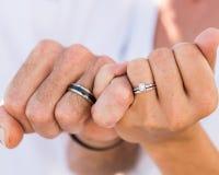 Bruid en bruidegomhanden die trouwringen tonen stock foto's