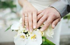 Bruid en bruidegomhanden met trouwringen Stock Foto's