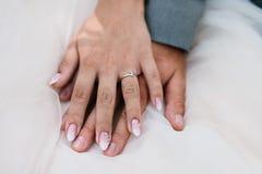 Bruid en bruidegomholdingshanden op de huwelijkskleding royalty-vrije stock foto's