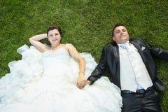 Bruid en bruidegomholdingshanden op gazon Stock Fotografie