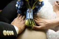 Bruid en bruidegomholdingshanden op huwelijksboeket bij auto Royalty-vrije Stock Foto's