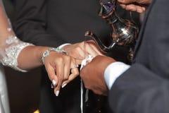 Bruid en bruidegomholdingshanden tijdens de traditionele Indische huwelijksceremonie Stock Afbeeldingen