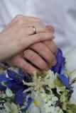 Bruid en bruidegomholdingshanden, trouwringen stock afbeeldingen