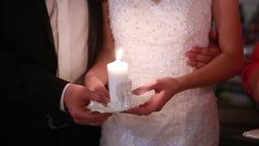 Bruid en bruidegomholdingskaarsen in hun handen stock video
