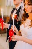 Bruid en bruidegomholdingskaarsen tijdens de traditionele huwelijksceremonie royalty-vrije stock foto's