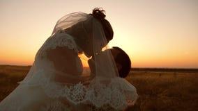 Bruid en bruidegomkus en omhelzing bij zonsondergang Tedere kussen in avonden tussen minnaars van de mens en vrouw stock video