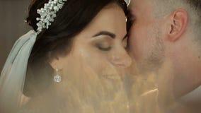 Bruid en bruidegomkussen teder in de schaduw van een vliegende sluier stock video