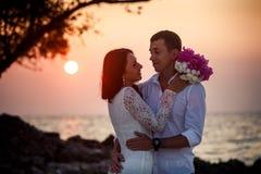 Bruid en bruidegomomhelzing bij strand bij dageraad Stock Fotografie