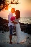 Bruid en bruidegomomhelzing bij strand bij zonsopgang Royalty-vrije Stock Afbeelding