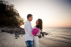 Bruid en bruidegomomhelzing bij zandstrand Stock Foto's