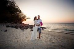 Bruid en bruidegomomhelzing bij zandstrand Royalty-vrije Stock Fotografie