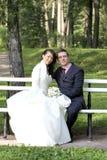 Bruid en bruidegomzitting op bank in park Stock Fotografie