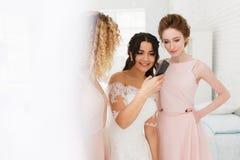 Bruid en bruidsmeisje die foto's op smartphone bespreken Ochtendvoorbereiding stock foto