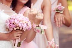 Bruid en bruidsmeisjeholdingsbloemen Royalty-vrije Stock Afbeeldingen