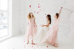 Bruid en bruidsmeisjes die in witte zolderstudio dansen met vliegende bloemblaadjes Volledig-lenght-hoogtepuntportret Royalty-vrije Stock Fotografie