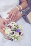 Bruid en van de bruidegom handen met huwelijksboeket royalty-vrije stock foto