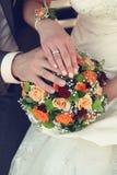 Bruid en van de bruidegom handen met trouwringen en boeket stock foto's