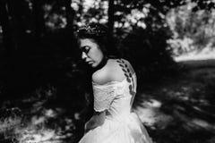 Bruid in het bos met schaduwbladeren Stock Foto