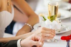 Bruid in het glas van de trouwringholding champagne ter beschikking Stock Foto's