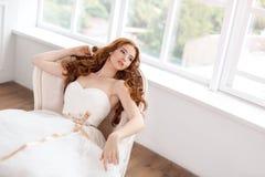 Bruid in het mooie kleding leggen die op bank binnen rusten Stock Afbeelding
