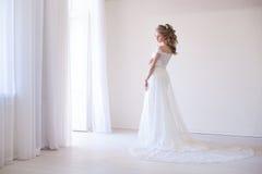 Bruid in huwelijkskleding in een witte ruimte stock fotografie