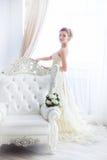 Bruid in huwelijkskleding en bloemen Royalty-vrije Stock Foto's