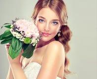Bruid in huwelijkskleding met bloemboeket stock afbeelding