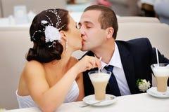 Bruid kussende bruidegom Stock Afbeeldingen