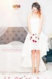 Bruid met Boeket Het bed van het slaapkamerhuwelijk stock fotografie