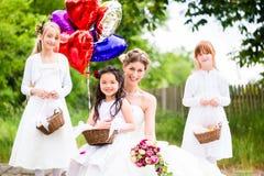 Bruid met meisjes als bruidsmeisjes, bloemen en ballons royalty-vrije stock foto