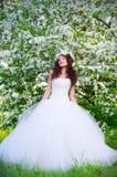 Bruid op de achtergrond van bloeiende appelbomen Stock Foto