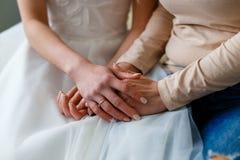 Bruid op haar huwelijksdag die haar moeder` s handen houden Concept van Royalty-vrije Stock Foto's