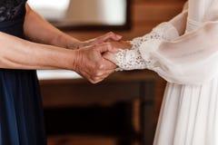 Bruid op huwelijksdag die haar moeder` s handen houden een oude vrouw houdt haar jonge dochter gehuwd stock afbeelding