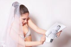 Bruid in sluieronderbreking de bruidegomfoto, grijze achtergrond Royalty-vrije Stock Afbeeldingen