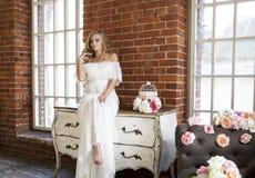 Bruid stellende zitting op uitstekende opmaker Stock Fotografie
