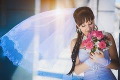 Bruid tegen een blauw modern gebouw Stock Afbeeldingen